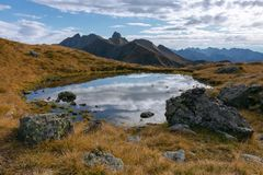 Autumnal alpine landscape with a small lake with a reflection of stock photos
