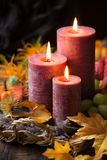 Autumnal arrangement with three lit candles and fall leaves Stock Photography