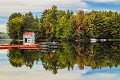 Autumnal Boathouse. A glass like reflection of a boathouse, sailboat and floats on Mary Lake in autumn Stock Photos