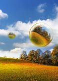 Autumnal bubbles and field. Illustration of floating bubbles reflecting colorful Autumnal countryside Stock Photo