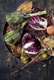 Autumnal composition on tray with raw artichokes and fresh red chicory with colored dry leaves Stock Images