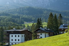 Autumnal corso Italia, the residential district in the town Cortina d`Ampezzo with meadow and mountain, Dolomite, Alps, Veneto. Italy, Europe Royalty Free Stock Image
