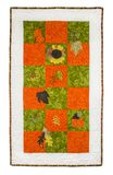 Autumnal flowers leaves theme quilt. Autumnal flowers and leaves theme quilt, on squares of material framed Stock Image