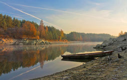 Autumnal forest.lonely old wooden boat near rocky coast of the r Stock Photos