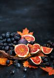 Autumnal fresh ripe figs and purple grape. On dark background stock photography