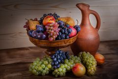 Autumnal fruit still life with Georgian jug on rustic wooden tab. Le background Royalty Free Stock Images