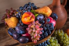 Autumnal fruit still life with Georgian jug on rustic wooden tab Stock Photo