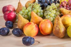 Autumnal fruit still life on rustic wooden table background Stock Photos