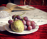 Autumnal fruits on the table with blurred objects in background Stock Photo