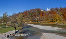 Autumnal hill with pilgrimage chapel, idyll at isar river bad to Stock Photography
