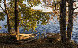 Autumnal lakeside. Beautiful sunny autumnal lakeside with two row boats Royalty Free Stock Image