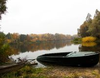 Autumnal landscape with tranquil river, old boats,bank,grass,trees,forest. Reflection stock images
