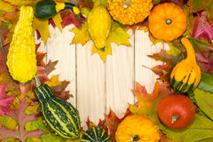 Autumnal leaves and pumpkins lying in heart shape on wooden boards Stock Photo