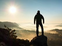 Autumnal  misty morning in nature. Hiker in black stand on peak in rock Royalty Free Stock Images