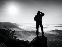 Autumnal  misty morning in nature. Hiker in black stand on peak in rock Royalty Free Stock Photos