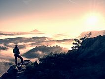 Autumnal  misty morning in nature. Hiker in black stand on peak in rock Royalty Free Stock Image