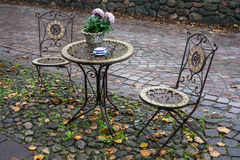 Autumnal mood in street. Autumnal scene, empty tables in street cafe in autumn with leaves stock images