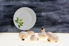 Autumnal Mushrooms with white background and gray wooden table and empty dish Royalty Free Stock Image