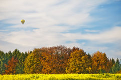 Autumnal sce with balloon. Hot-air balloon with autumnal painted forest royalty free stock photo
