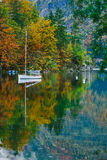 Autumnal scenic view of boats on the Bohinj lake surrounded by colorful forest. Slovenia, Europe Royalty Free Stock Photography