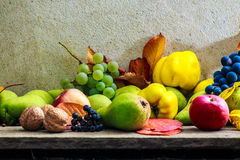 Autumnal still life with fruit and leaves on a wooden base Stock Photo