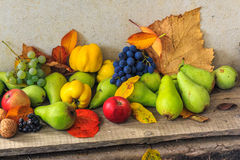 Autumnal still life with fruit and leaves on a wooden base Royalty Free Stock Images