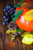 Autumnal still life with pumpkin and grapes on wooden board Stock Photo