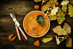 Autumnal table setting for Thanksgiving dinner. Empty plate, cutlery, colored leaves on wooden table. Fall food concept. Autumnal table setting for Thanksgiving royalty free stock photo