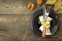 Autumnal table setting for Thanksgiving dinner. Empty plate, cutlery, colored leaves on wooden table. Fall food concept. Autumnal table setting for Thanksgiving stock images