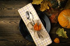Autumnal table setting for Thanksgiving dinner. Empty plate, cutlery, colored leaves on wooden table. Fall food concept. Autumnal table setting for Thanksgiving stock photos