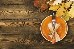 Autumnal table setting for Thanksgiving dinner. Empty plate, cutlery, colored leaves on wooden table. Fall food concept. Autumnal table setting for Thanksgiving royalty free stock photos