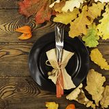 Autumnal table setting for Thanksgiving dinner. Empty plate, cutlery, colored leaves on wooden table. Fall food concept. Autumnal table setting for Thanksgiving royalty free stock image