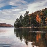 Trees reflected in a lake. Autumnal trees reflected in the lake at Gatineau Park, Canada Royalty Free Stock Image