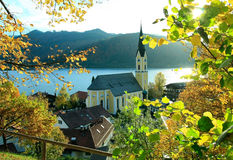 Autumnal view through branches to schliersee lake and church Royalty Free Stock Photography