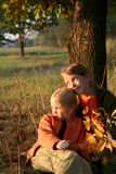 Autumnal walk. Two girls sitting under the tree Stock Image
