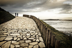 Autumnal walk. Couple and their dog in silhouette walking along a paved way to shore of the sea. The cloudy day and the hot dominant color they give a romantic Royalty Free Stock Photo