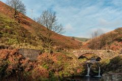 An autumnal waterfall and stone packhorse bridge at Three Shires royalty free stock photo