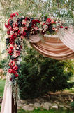 Autumnal wedding arch decoration of roses, apples, grape and pomergranate. In red colour, closeup Royalty Free Stock Images