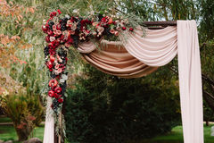 Autumnal wedding arch decoration of roses, apples, grape and pomergranate. In red colour, closeup Stock Photos
