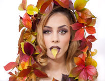 Autumnal woman. Beautiful creative makeup and hair style in fall concept studio shot. Beauty fashion model girl with fall makeup Royalty Free Stock Images