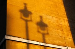 Autumnul orange sunset light casts shadow of 2 street lamps on the side of a London limestone building royalty free stock image