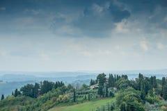 Autunno in anticipo del paesaggio toscano con le case ed il cielo drammatico Fotografia Stock