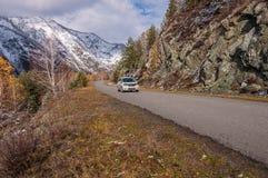Autunno della neve delle montagne della strada di guida di veicoli Fotografia Stock