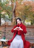 Autunno magico, donna di caduta felice e beatitudine, bella donna che si siede su un banco nel parco di autunno Immagini Stock Libere da Diritti
