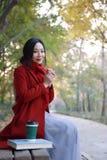 Autunno magico, donna di caduta felice e beatitudine, bella donna che si siede su un banco nel parco di autunno Fotografia Stock