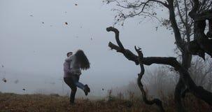 Autunno scuro, paesaggio della montagna L'uomo gira la donna prima degli alberi con le foglie cadute coperte di nebbia pesante video d archivio