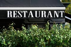 Auvent de restaurant avec le buisson Image stock