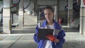 Auxílio da jovem mulher que redige a informação importante sobre o carro para o teste e o controle no serviço moderno do carro filme
