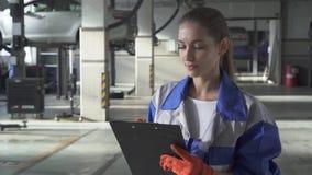 Auxílio da jovem mulher que redige a informação importante sobre o carro para o teste e o controle no serviço moderno do carro video estoque