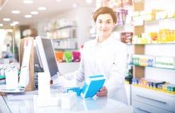Auxílio de oferecimento do farmacêutico fêmea no contador na farmácia foto de stock royalty free